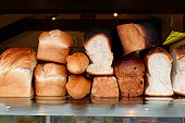 Loaves of fresh bread piled on a bakery counter.