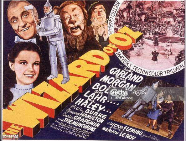 A lobby card from the film 'The Wizard Of Oz' shows an illustration of American actress Judy Garland and left to right actors Frank Morgan Jack Haley...