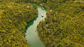 Aerial view, River in the rainforest among the jungle Tropical Loboc river in the rain forest in Asia. Mountain river flows through green forest. Philippines, Bohol.