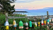 Lobster Buoys Hanging on Fence, Maine Rocky Coast Shore at twilight sunset evening time.