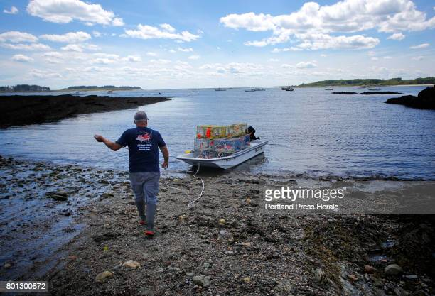 Lobsterman Ted Gilfillan launches a boatfull of traps before heading out on the water at Kettle Cove on Thursday June 22 2017