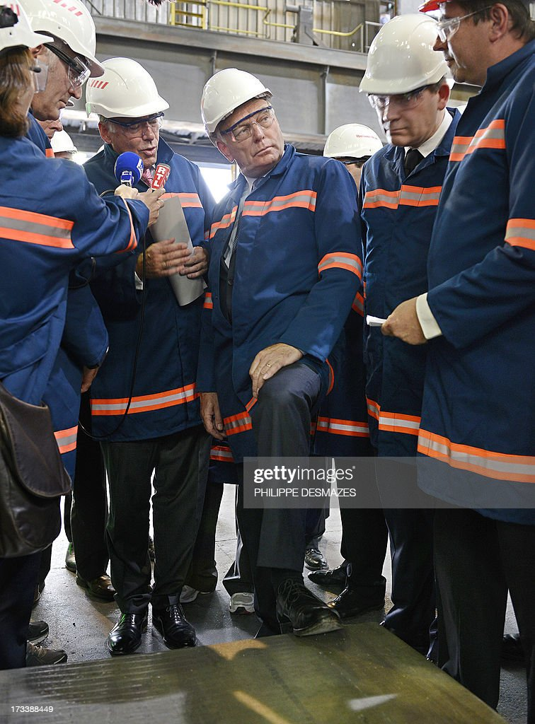 Loïc Maenner (L), director of Rio Tinto, talks with French Minister for Industrial Renewal and Food Industry Arnaud Montebourg (2ndL), French Prime minister Jean-Marc Ayrault (C) and german Heinz-Peter Schlüter as they visit the Rio Tinto Alcan (RTA) aluminum factory in Saint-Jean-de-Maurienne, southeast of France, on July 13, 2013. Heads of Rio Tinto Alcan and Germany's Trimet met today in Paris regarding the take over of RTA by Trimet which could save 510 jobs at the two sites of Saint-Jean-de-Maurienne (Savoie) and Castelsarrasin (Tarn-et-Garonne) .