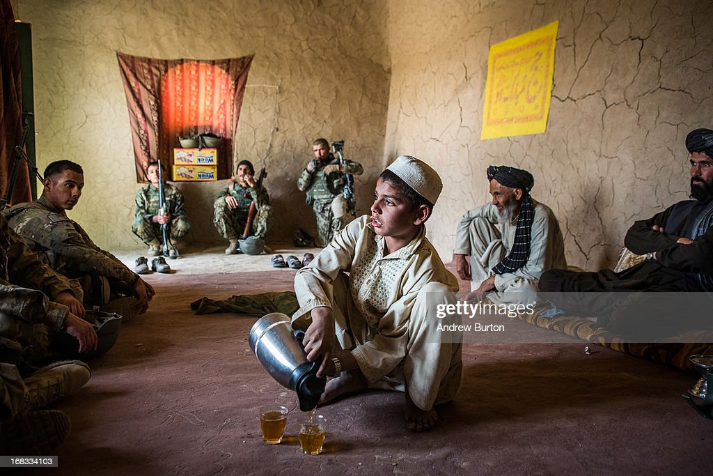 A local Afghan boy pours tea for soldiers and during a joint patrol between the Afghan National Army's 6th Kandak (battalion), 3rd company and the U.S. Army's 1st Battalion, 36th Infantry Regiment near Command Outpost Pa'in Kalay on April 3, 2013 in Kandahar Province, Maiwand District, Afghanistan. The United States military and its allies are in the midst of training and transitioning power to the Afghan National Security Forces in order to withdraw from the country by 2014.