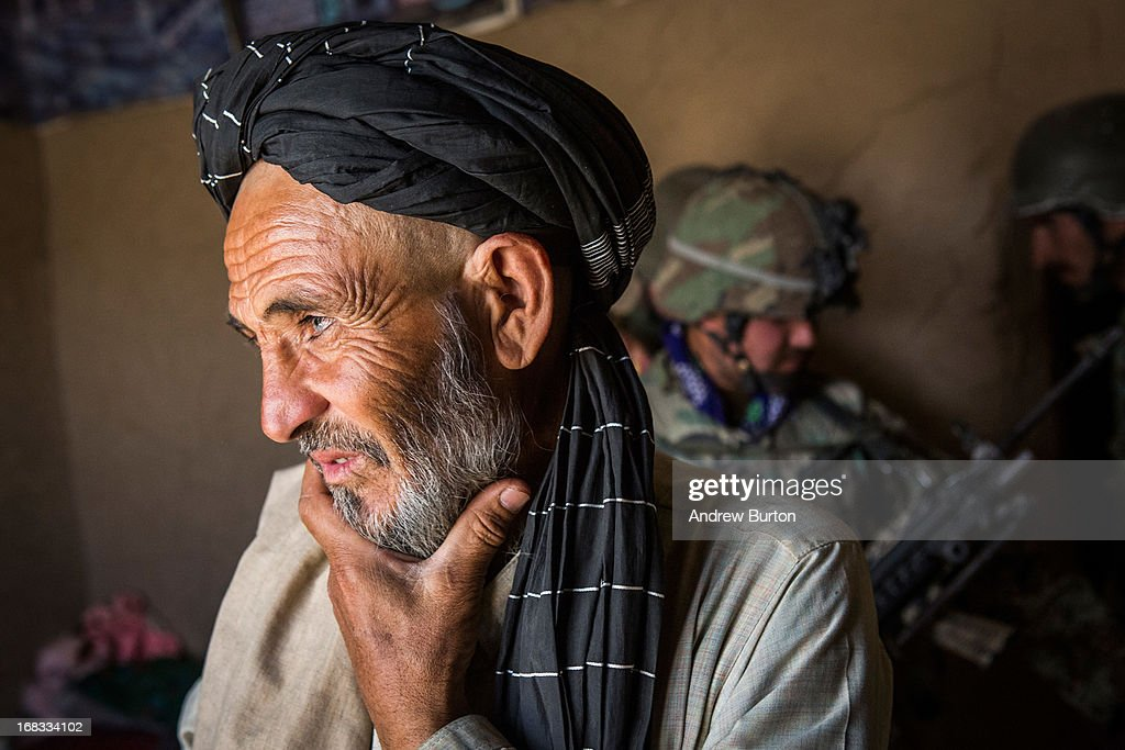 A local Afghan man waits while soldiers in the Afghan National Army's 6th Kandak (battalion), 3rd company search his home during a joint patrol with the U.S. Army's 1st Battalion, 36th Infantry Regiment near Command Outpost Pa'in Kalay on April 3, 2013 in Kandahar Province, Maiwand District, Afghanistan. The United States military and its allies are in the midst of training and transitioning power to the Afghan National Security Forces in order to withdraw from the country by 2014.