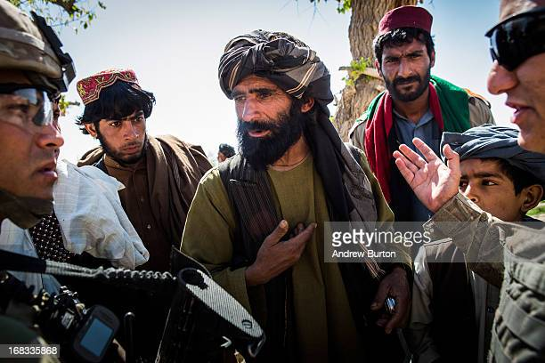 Local Afghan men speak to a soldier in the United States Army's 3rd Battalion 41st Infantry Regiment during a joint patrol with the Afghan National...