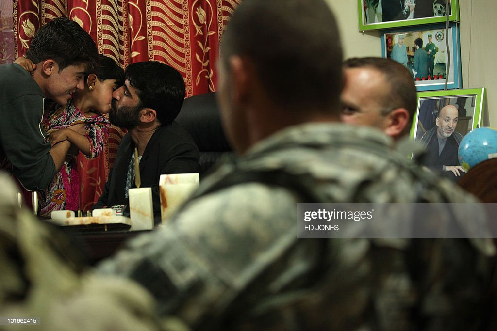A local Afghan police commandant kisses a child as he sits with US soldiers at a police station in Kandahar city on June 6, 2010. The US and NATO are boosting to 150,000 the number of foreign troops in Afghanistan by August 2010 as they build up operations to beat back the Taliban from around their spiritual home of Kandahar in the south.