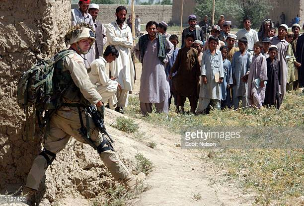 Local Afghans watch as a US Army soldier from the 101st Airborne blocks a footpath during 'sensitive site exploitation' mission or SSE July 16 2002...