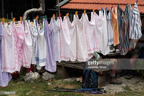 Local alpine dairy farmers sit on a bench behind freshly washed laundry waiting for German Agriculture Minister Ilse Aigner hiking up to an alpine...