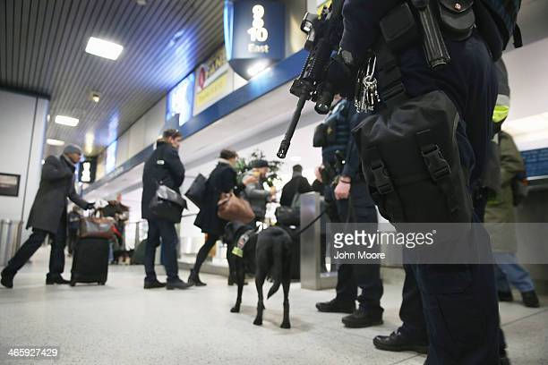 Local and federal law enforcement agents stand guard at Manhattan's Penn Station as people line up to board a train on January 30 2014 in New York...