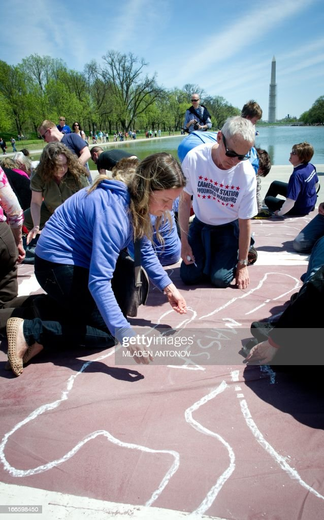 "Local artists trace an outline of their bodies with chalk to represent persons killed by guns, at the Lincoln Memorial reflecting pool as they take part in a 'flash mob' performance in protest against gun violence in the US, April 14, 2013 in Washington DC. According to the organizers the ""art-meets-flash mob"" performance is a visual reflection of the destruction caused by gun violence."