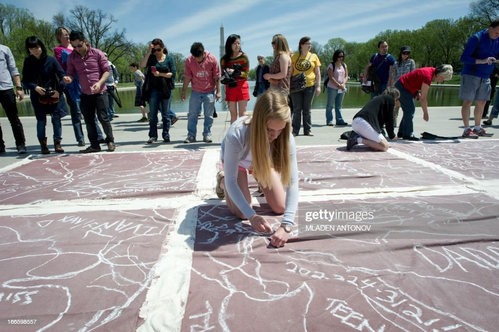 "Local artists trace an outline of their bodies with chalk to represent persons killed by guns, at the Lincoln Memorial reflecting pool as they take part in a 'flash mob' performance in protest against gun violence in the US, April 14, 2013 in Washington DC. According to the organizers the ""art-meets-flash mob"" performance is a visual reflection of the destruction caused by gun violence. AFP PHOTO / MLADEN ANTONOV"