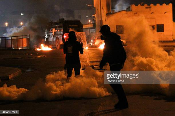 Local Bahraini protester holds a shield during the repression of tear gas clashes in Bahraini regime forces after the issuance of the death sentence...