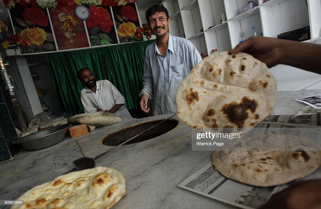Local bakers talk with customers while making chapati on April 30 in Islamabad Pakistan Pakistan is experiencing a major shortage of wheat causing...