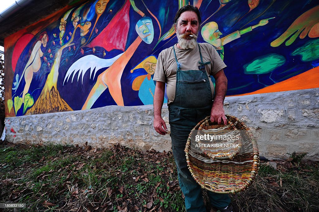 A local basket maker shows his products in front of a fresco of a house in a gipsy village Bodvalenke nearby the Hungarian and Slovakian border on October 22, 2013. The Hungarian Reformed Church Aid Foundations 'Bodvalenke Fresco Village' project was launched in 2009 and the first phase of the project is finished this weekend with the 33rd fresco. The project, which is unique in the world, it wished to contribute to the reduction of prejudices by presenting the works of Roma painters and to help the villagers to combat the extreme poverty they have been living in by turning Bodvalenke into an attractive tourist destination.