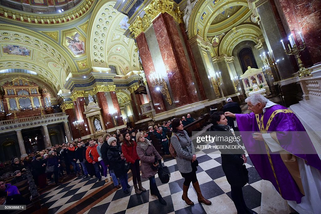 Local beleivers receive the ash-cross, given by father Attila Farkas (R) during a mass in the St Stephan Basilica at the beginning of Lent, which starts 40 days before Easter on February 10, 2016 during an evening mass for Ash Wednesday in Budapest, Hungary. / AFP / ATTILA KISBENEDEK
