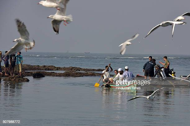 A local boat carries the body of the 14th and the last student recovered by rescue team to the shore at MurudJanjira beach at the Arabian Sea coast...