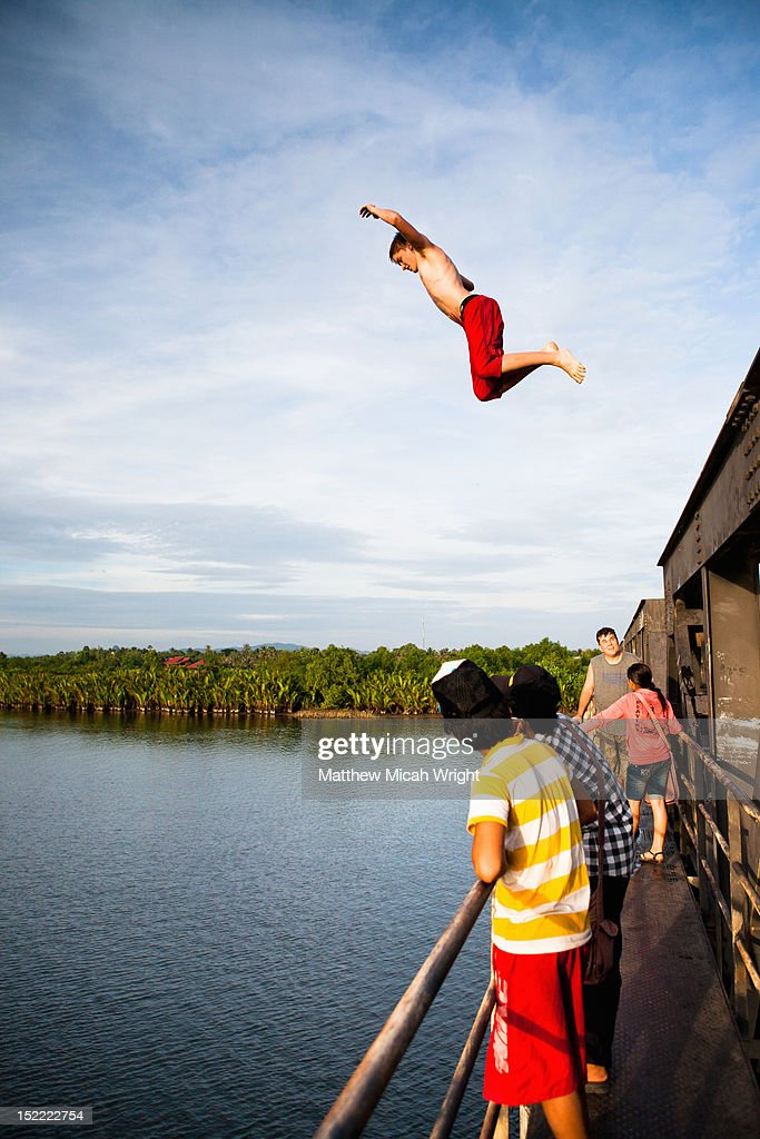 A local boy jumps from a high bridge. : Stock Photo