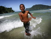 A local boy runs out from the sea after diving from a fishing boat at Maracas Bay on March 2 2008 near Port of Spain Trinidad and Tobago With it's...