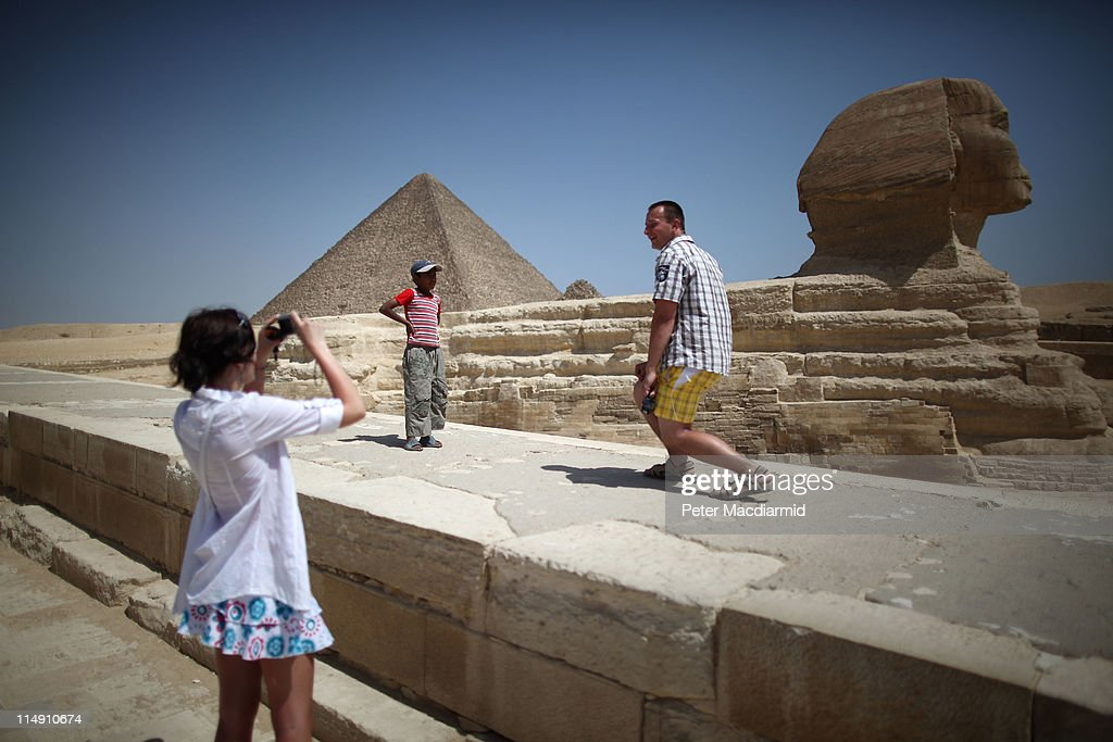 A local boy watches as tourists photograph themselves at the Sphinx and the great Pyramid of Cheops on May 28, 2011 in Giza, Egypt. Protests in January and February brought an end to 30 years of autocratic rule by President Hosni Mubarak who will now face trial. Food prices have doubled and youth unemployment stands at 30%. Tourism is yet to return to pre-uprising levels.
