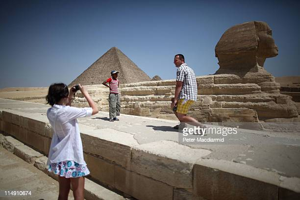 A local boy watches as tourists photograph themselves at the Sphinx and the great Pyramid of Cheops on May 28 2011 in Giza Egypt Protests in January...