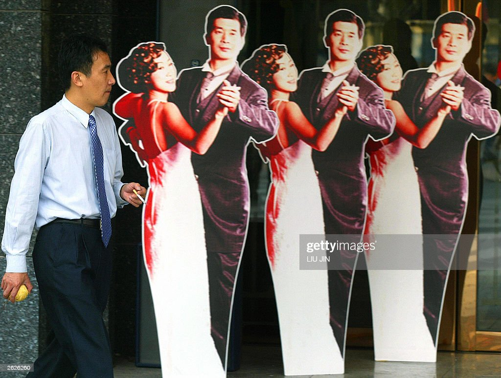 A local businessman walks past the human lifesize paperboard advertisements promoting Hong Kong's goods in Shanghai 22 October 2003 Shanghai Mayor...