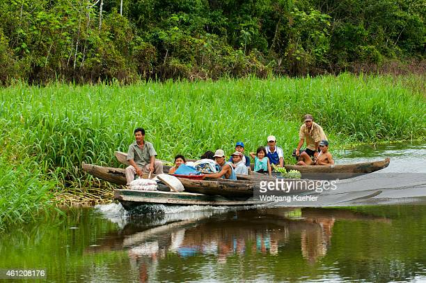 Local cabocolo people with their canoes traveling in a wooden motorized boat a small river in the Peruvian Amazon River basin near Iquitos