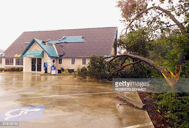 A local cafeteria in New Smyrna Beach FL sits with its roof shingles blown off by near hurricane winds 15 September 1999 as Hurricane Floyd heads...