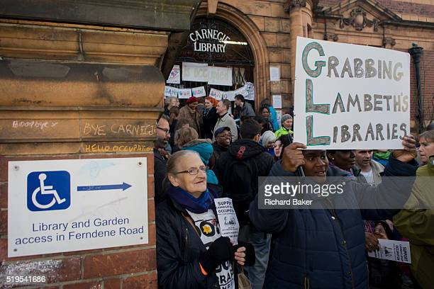 Local campaigners gather outside while protesting on the steps of Carnegie Library in Herne Hill south London while occupiers remain inside the...
