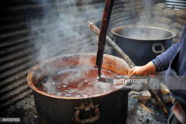 A local checks the molten raw hardened molasses or Chaku for the celebration of Maghe Sankranti Festival on January 15 2015 Molasses Chaku is usually...