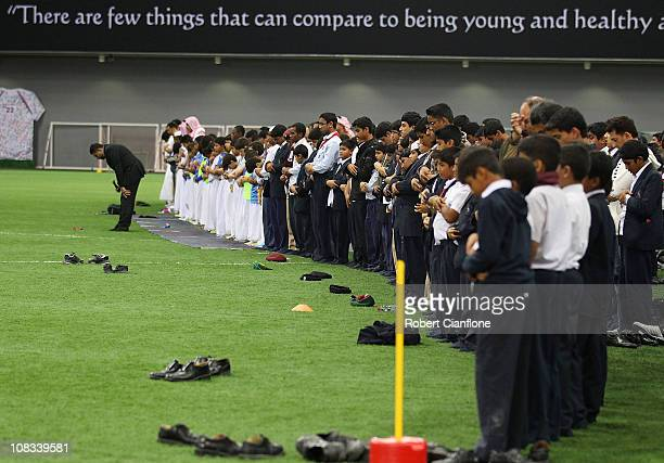 Local children and their families take time out to pray at a football training session at the ASPIRE Academy for Sports Excellence on January 25 2011...