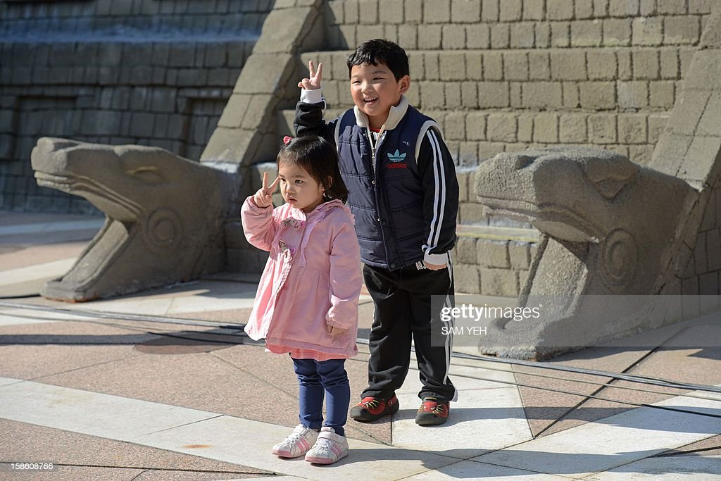 Local children cheer in front of a replica of a Mayan pyramid before a count-down ceremony organized by the National Museum of Natural Science to help ensure the public it is not the end of the world, in central Taichung on December 21, 2012. A digital 'doomsday clock' on top of a two-storey replica Mayan pyramid erected at a museum in central Taiwan's Taichung city completed its countdown for the end of the world at 0600 GMT -- midnight in Mexico. AFP PHOTO / Sam Yeh