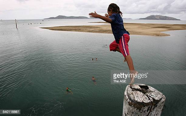 Local children fill in their spare time by jumping off the pier on Palm Island in northern Queensland 18 January 2007 THE AGE Picture by PAUL HARRIS