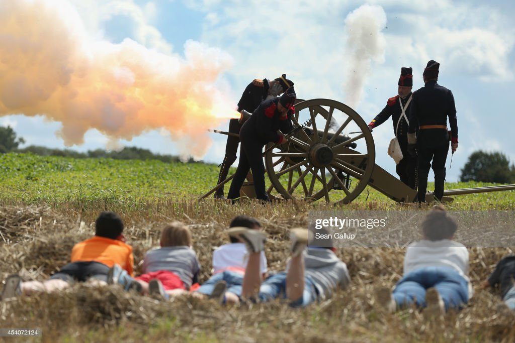 Local children lie in the grass as they watch historical society members fire five volleys of a cannon at the inauguration ceremony of a monument to honour members of the British Cheshire Regiment and other soldiers who died fighting the German Army exactly 100 years before at the same site during World War I on August 24, 2014 in Audregnies, Belgium. Of the 25 officers and 925 men of the 1st Battalion, Cheshire Regiment who fought that day on August 24, 1914, only a total of 207 would survive after two messengers with instructions for the unit to retreat failed to make it through. The battle came on the heals of the Battle of Mons the day before, which was the first major engagmement between British and German forces in the war. The British, French and Belgian armies were forced to continue their retreat until weeks later, when only a short distance from Paris they managed to reverse the tide of the war and push the Germans back north.