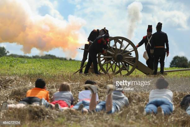 Local children lie in the grass as they watch historical society members fire five volleys of a cannon at the inauguration ceremony of a monument to...