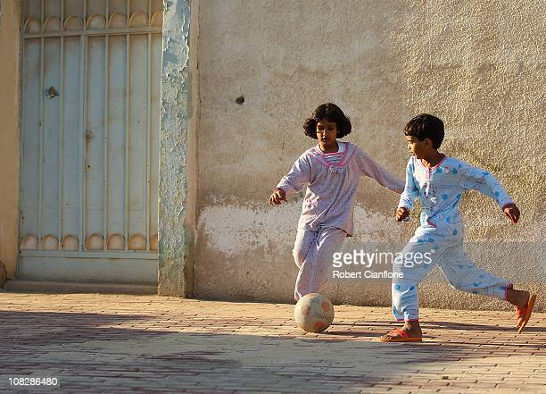 Local children play football on a local street in Doha on January 24 2011 in Doha Qatar
