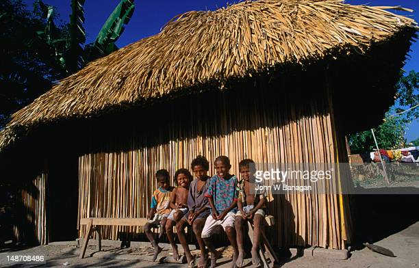 Local children sitting in front a traditional house, Maubara.