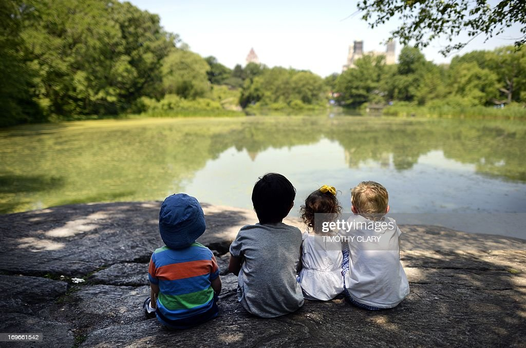 Local children take advantage of the hot weather to sun on a rock at the Lower Reservoir near the Belvedere Castle in Central Park on May 30, 2013 as temperatures were expected to reach in the 90's (30C) in New York City. AFP PHOTO / TIMOTHY CLARY