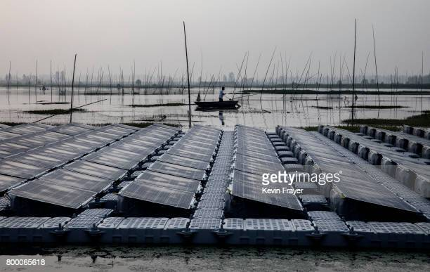 A local Chinese fisherman passes a section of a large floating solar farm project under construction by the Sungrow Power Supply Company on a lake...