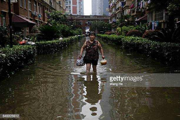 Local Chinese residents walk on a flooded street in South Lake Community of Wuhan Hubei Province of China on July 7 2016 in Wuhan China
