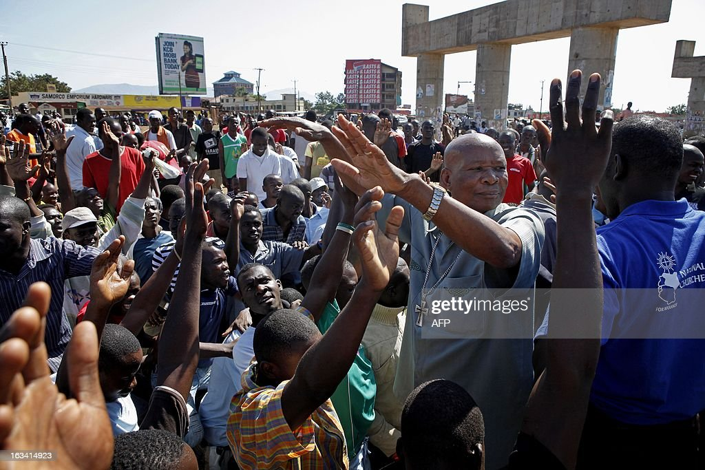 A local church leader (R) appeals a crowd of angry residents to stay calm at Kondele slum in Kisumu, ahead of the official declaration of the final results of the presidential elections on March 9, 2013. Uhuru Kenyatta was named outright winner of the elections with an overall majority of 50.07%, but his opponent, Raila Odinga, said that he will contest the results in the Supreme Court. AFP PHOTO / TILL MUELLENMEISTER