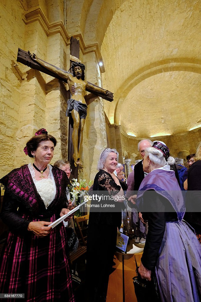 Local church members stand under a crucifix after a church service on May 25, 2016 in Saintes-Maries-de-la-Mer near Arles, France. Gypsies from all over Europe worship 'Sara the Black', their Saint and patroness, for one week. Sara's statue is situated in the crypt of the church.