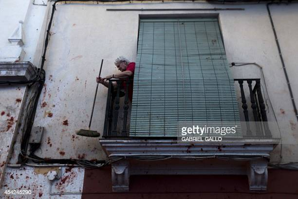 A local cleans tomato pulp from a wall during the annual 'tomatina' festivities in the village of Bunol near Valencia on August 27 2014 Some 22000...