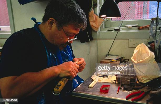 Local craftsman carving narwhal bone into jewellery.