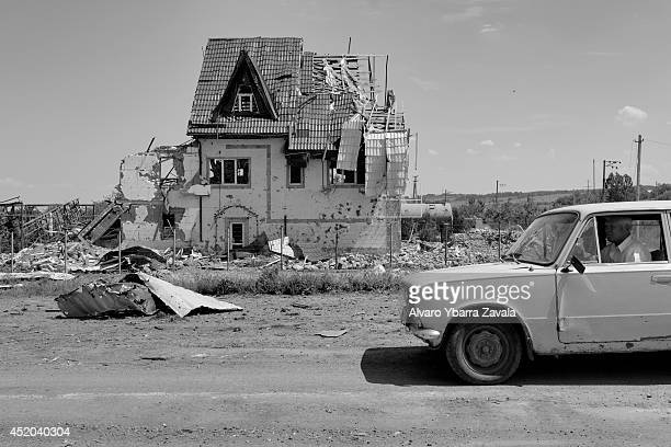 A local driver passes a destroyed house on July 11 2014 in the village of Semyonovka near the eastern Ukrainian city of Slavyansk Russian and...