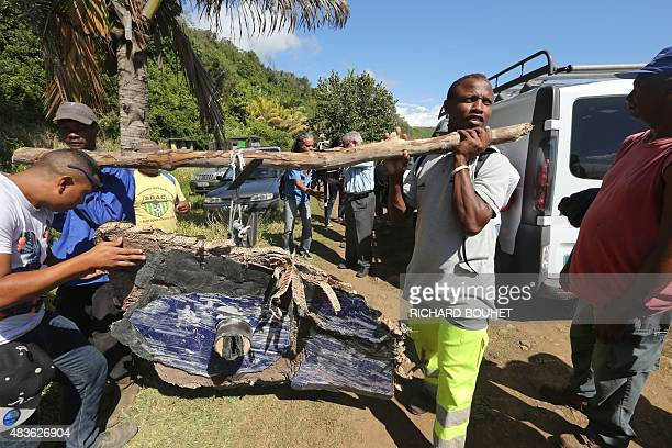 Local ecological association members and volunteers carry debris found on August 11 2015 in the eastern part of SainteSuzanne on France's Reunion...