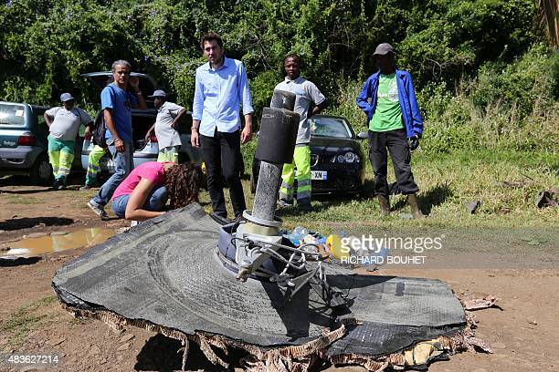 Local ecological association members and volunteers stand behind debris found on August 11 2015 in the eastern part of SainteSuzanne on France's...
