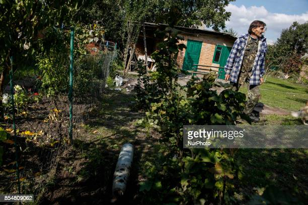 A local elderly is seen standing next to the Multiple launcher rocket part near his house September 27 2017 Ammunition depots in the town of...