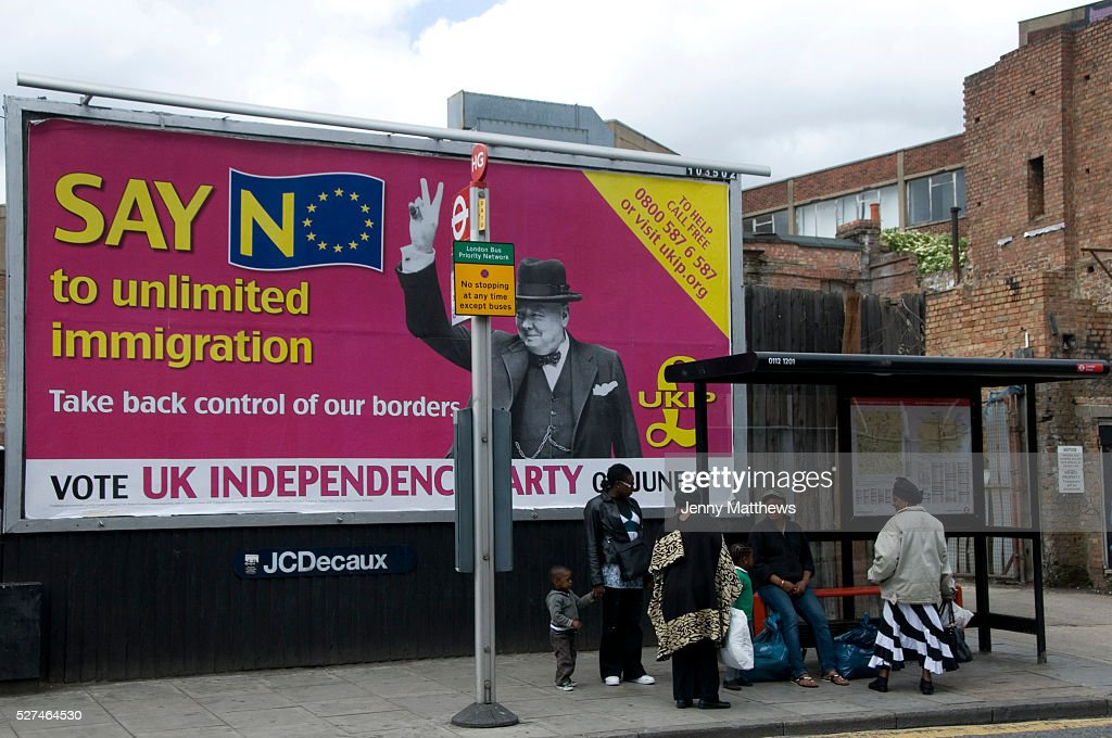 2009 local election Poster for UKIP with picture of Churchill and slogan 'Say No to unlimited immigration ' in front of a bus stop where black family...