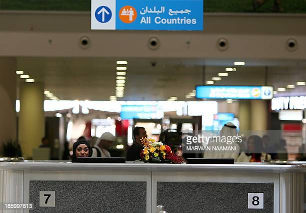 A local employee sits at the passport control at the newly opened AlMaktoum International airport the emirate's second airport in Dubai on October 27...