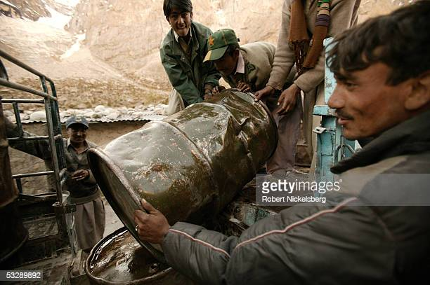 Local ethnic Balti laborers transfer kerosene fuel barrels for delivery to a higher altitude military base at 13800 feet June 17 2005 in Gyari...
